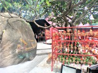 A boulder with a carved and painted ship lies beside the prayer pegs at A-Ma Temple, Macau